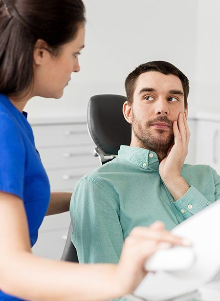 Man in dental chair for emergency dentistry holding jaw