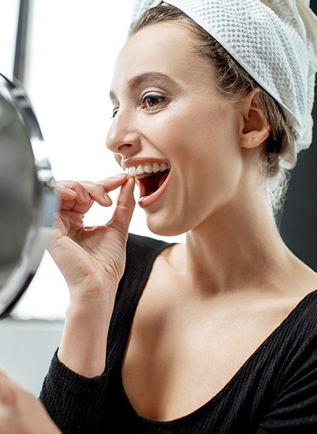 Woman looking at smile with Invisalign tray in place