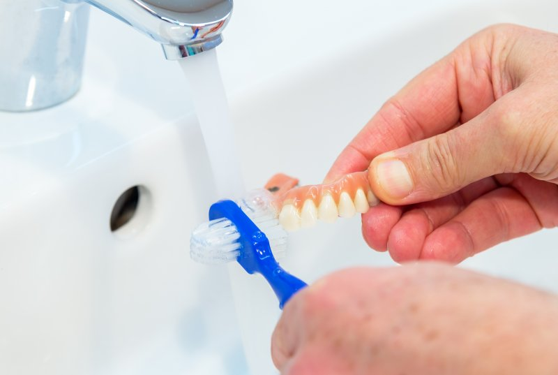 a person using a denture brush to clean their full denture