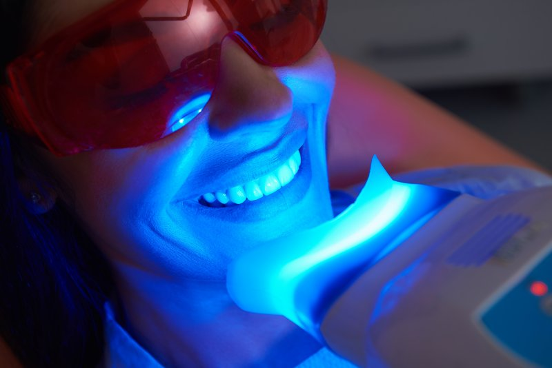 Smiling woman getting professional teeth whitening in Manchester